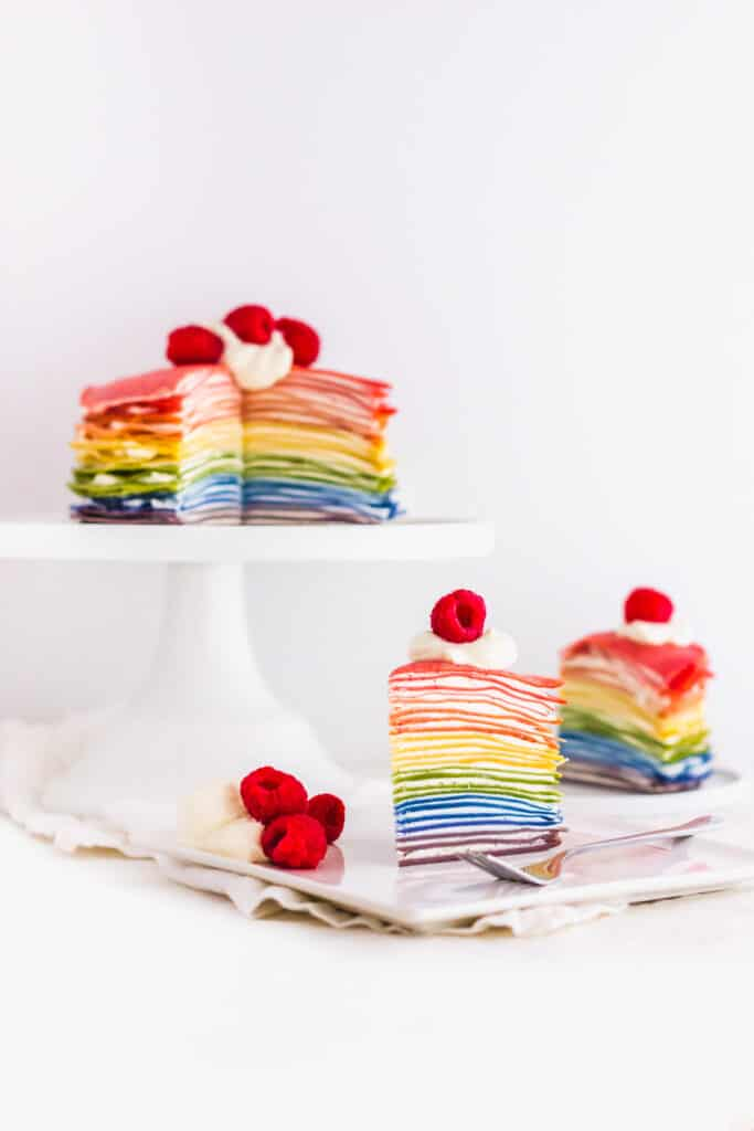 Slice of rainbow Mille Crepe Cake on square plate with fork, cake in background.
