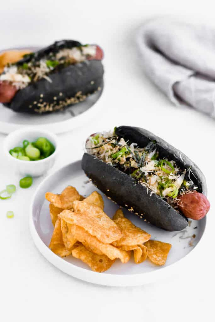 Black charcoal hotdog bun on white round plate with chips.