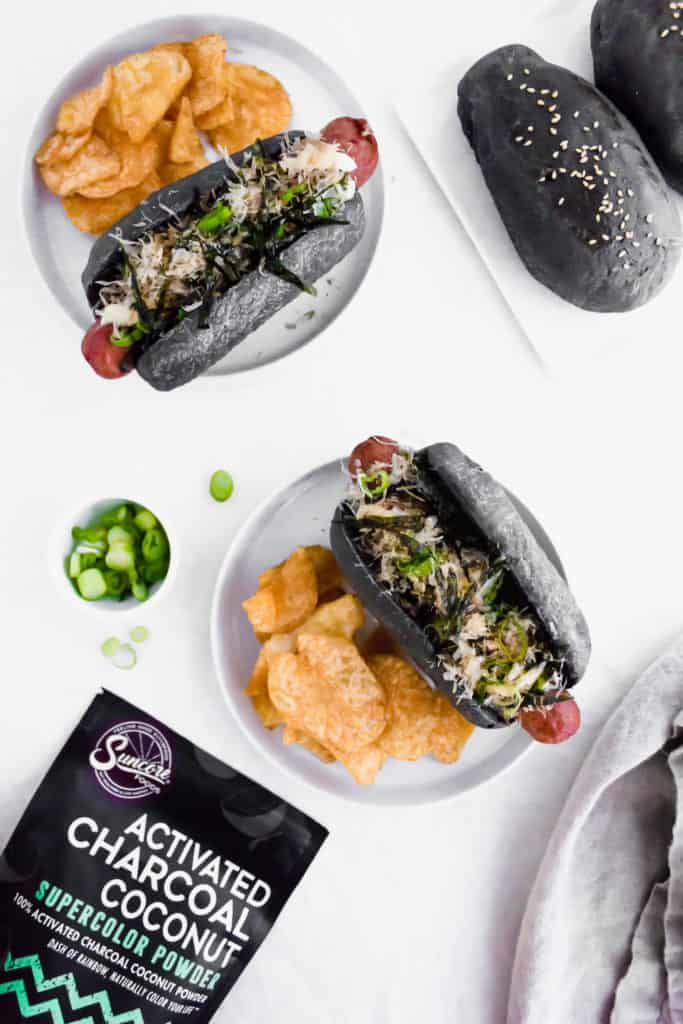 Black charcoal hotdog bun on white round plate with chips, with powder packaging.
