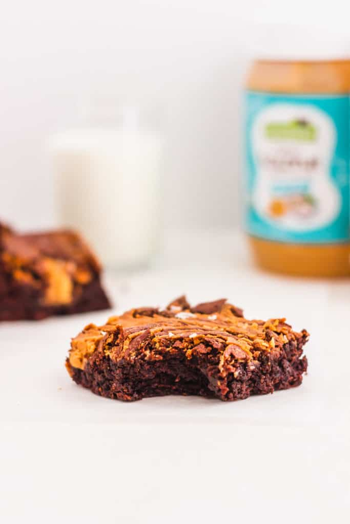 A bitten Coconut Peanut Butter Chocolate Brownie, glass of milk, packaging in back.