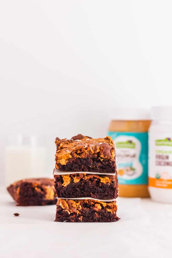 Stack of Coconut Peanut Butter Chocolate Brownies, packaging in back.