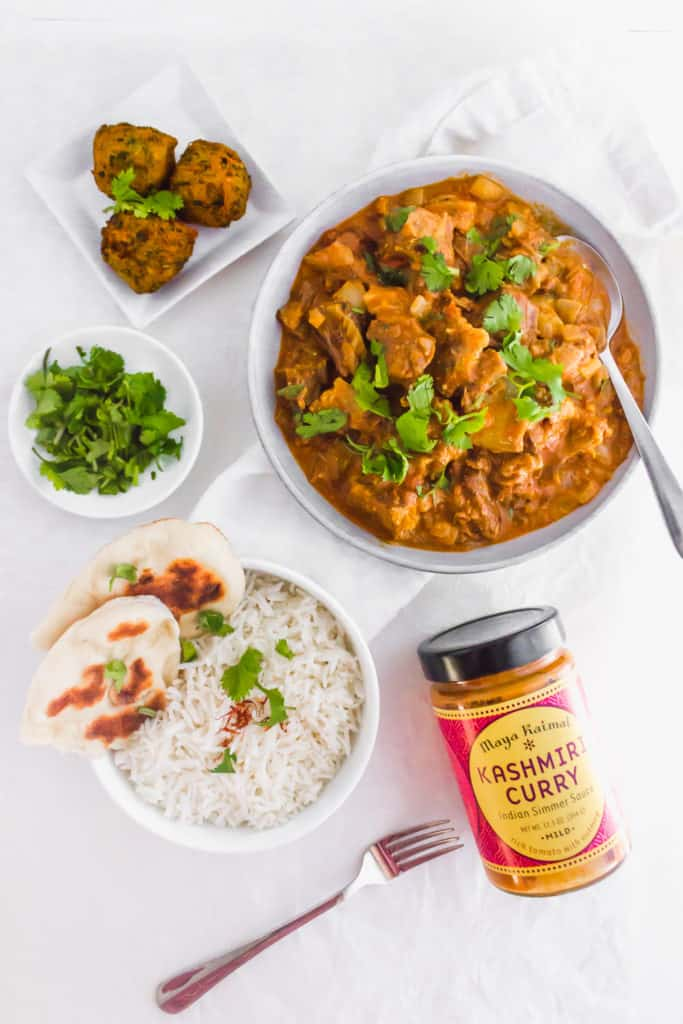 Large dish of Kashmiri Beef Short Rib Curry, small bowl of rice with fork on side, jar of Kashmiri Curry on side.
