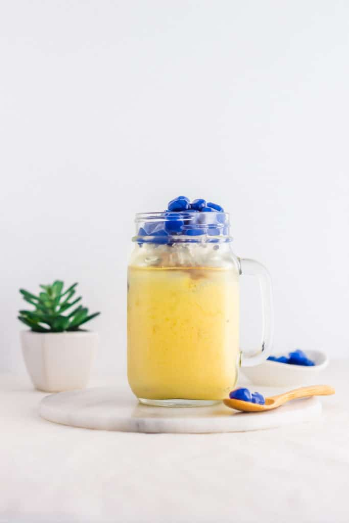 Glass jar of Mango Jasmine and Butterfly Pea Pearl Bubble Tea on marble trivet, spoon of blue boba pears on side.