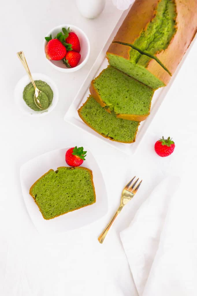 Slice of matcha pound cake on small plate, golden fork on side, cake in background.