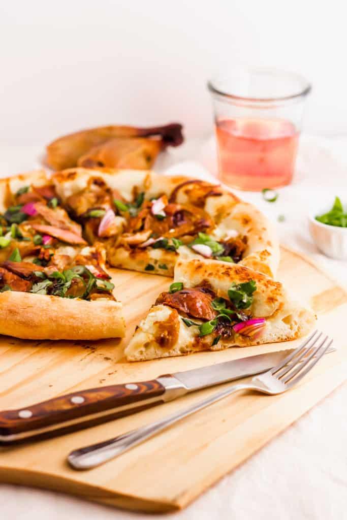 Close up of a slice of peking duck pizza on wooden pizza board, with knife and fork.