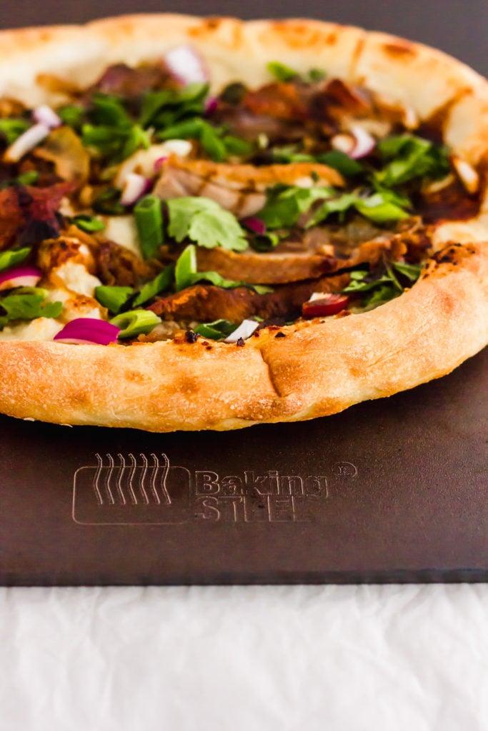 Close up of peking duck pizza on baking steel.