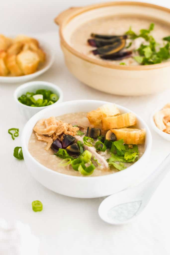 Close up of preserved century egg pork congee in white bowl, with spoon on side.