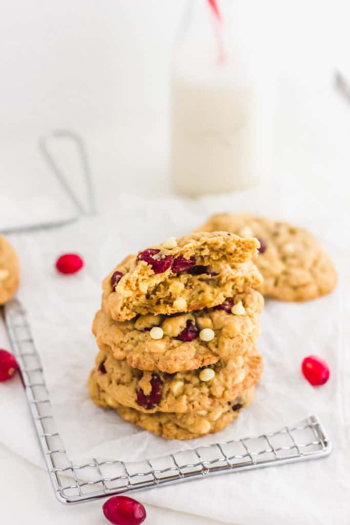 Stack of White Chocolate Cranberry Cookies with glass of milk and red and white straw in background.