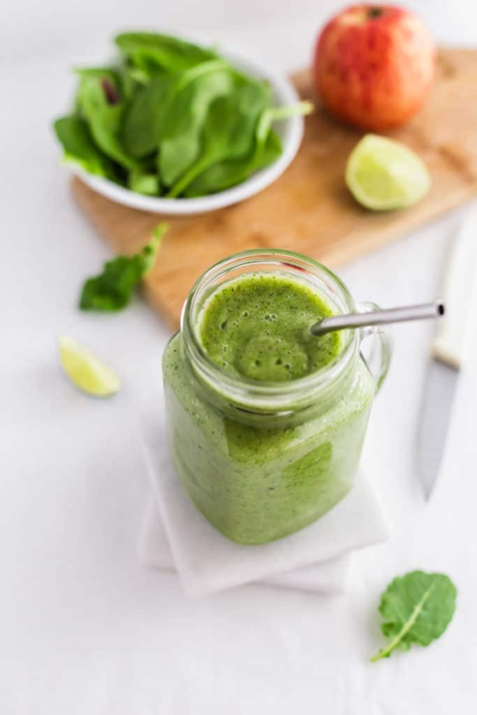 Close up of Green Smoothie in jar with metal straw on marble coasters, leafy greens on side..