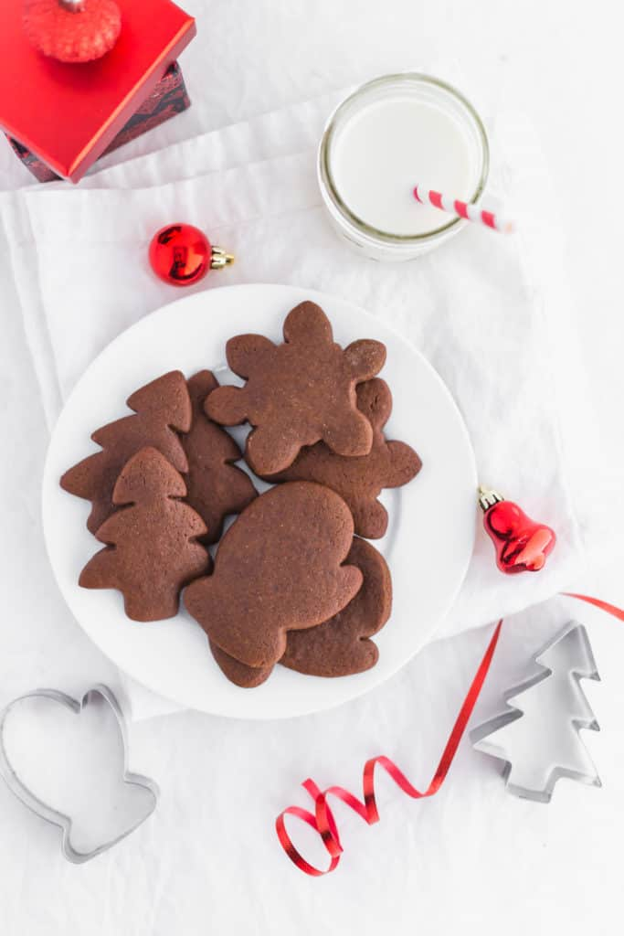 Gingerbread Cardamom Cookies on white plate with cookie cutters, glass of milk with red and white straw.