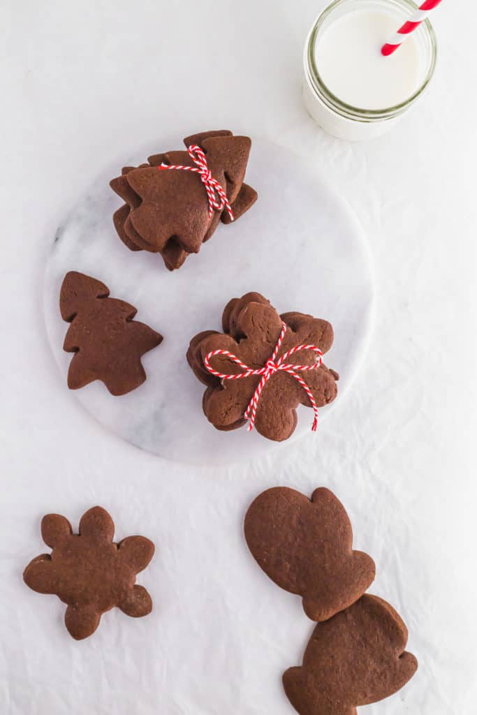 Gingerbread Cardamom Cookies on marble trivet glass of milk with red and white straw.