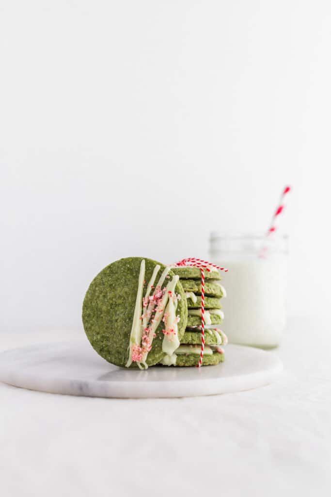 Matcha White Chocolate Peppermint Cookies on round marble board, glass of milk with straw in background.