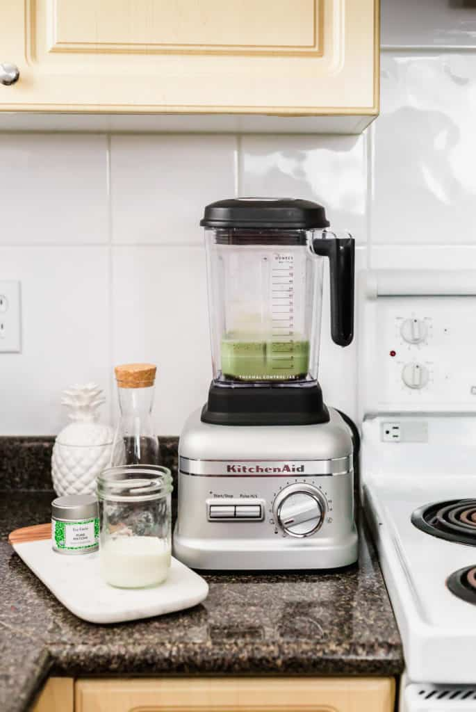 KitchenAid blender with matcha latte, on kitchen counter, glass of milk on side.