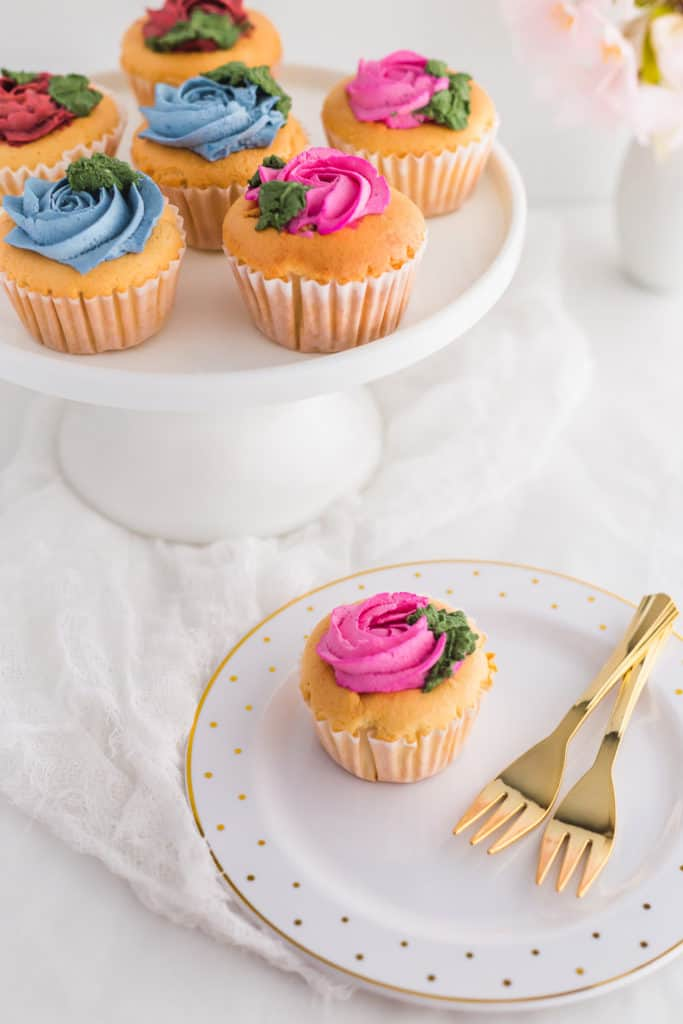 Hokkaido cupcake on plate with forks, cupcakes on stand in background.