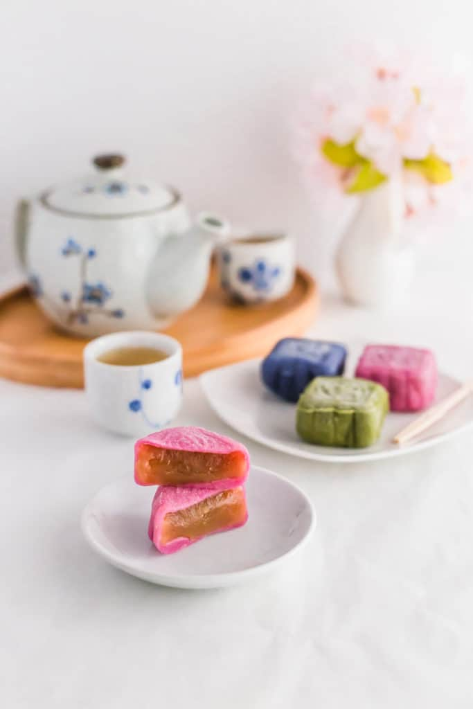 Cut pink Snowskin Mooncakes on small white dish.