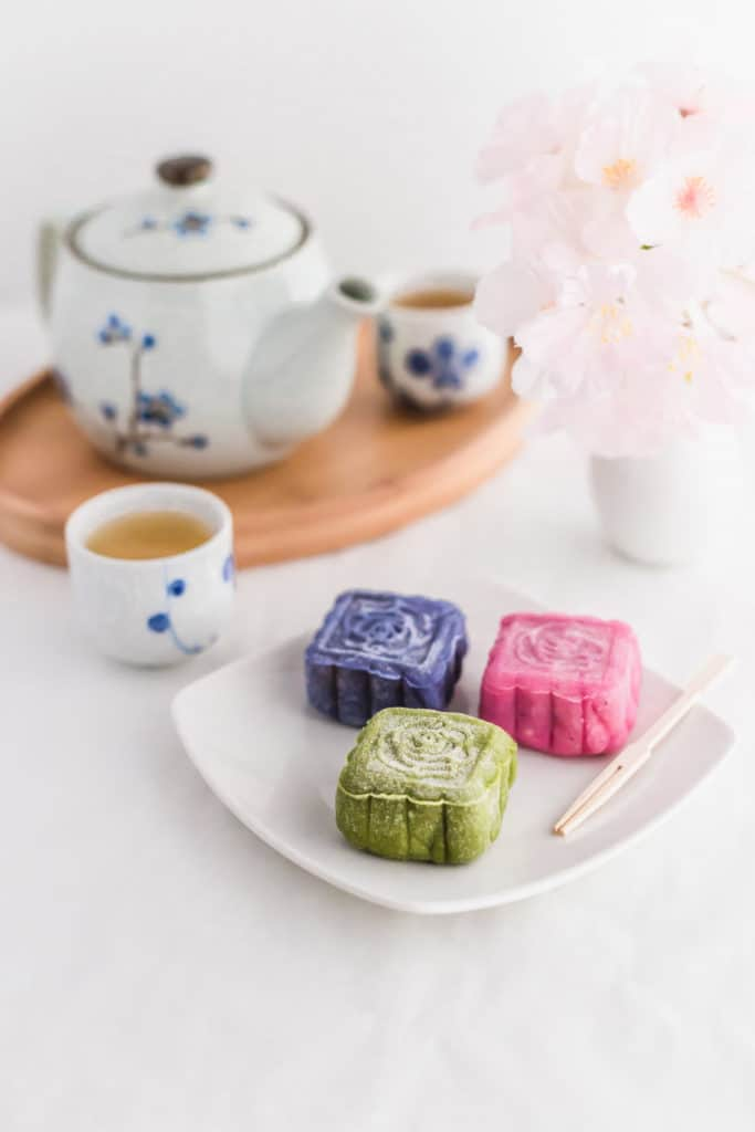Coloured Snowskin Mooncakes on small white plate, with toothpick.