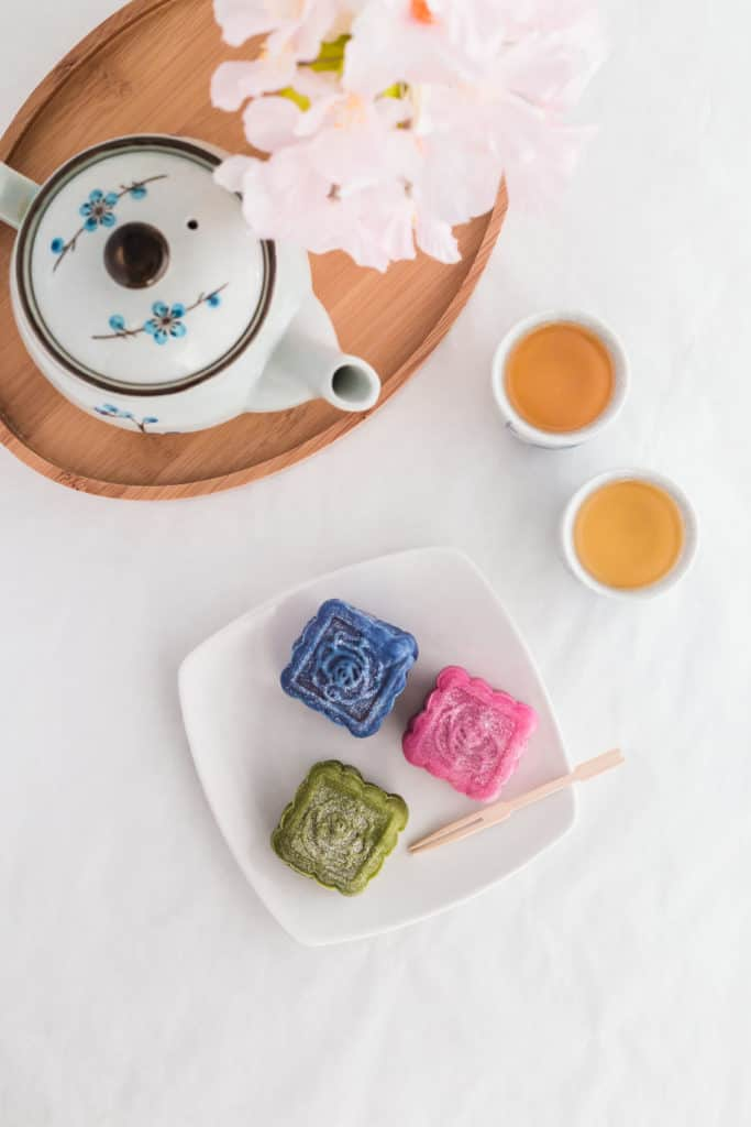 Coloured Snowskin Mooncakes on small white plate, with toothpick, tea cups on side.