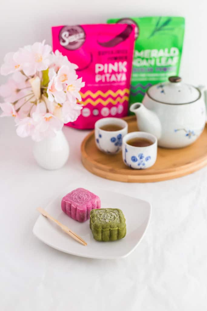 Coloured Snowskin Mooncakes on small white plate, with toothpick, coloured powder packaging in background.