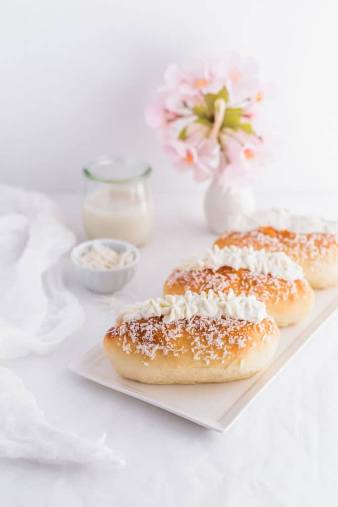 Coconut Cream Buns lined up on rectangular plate.
