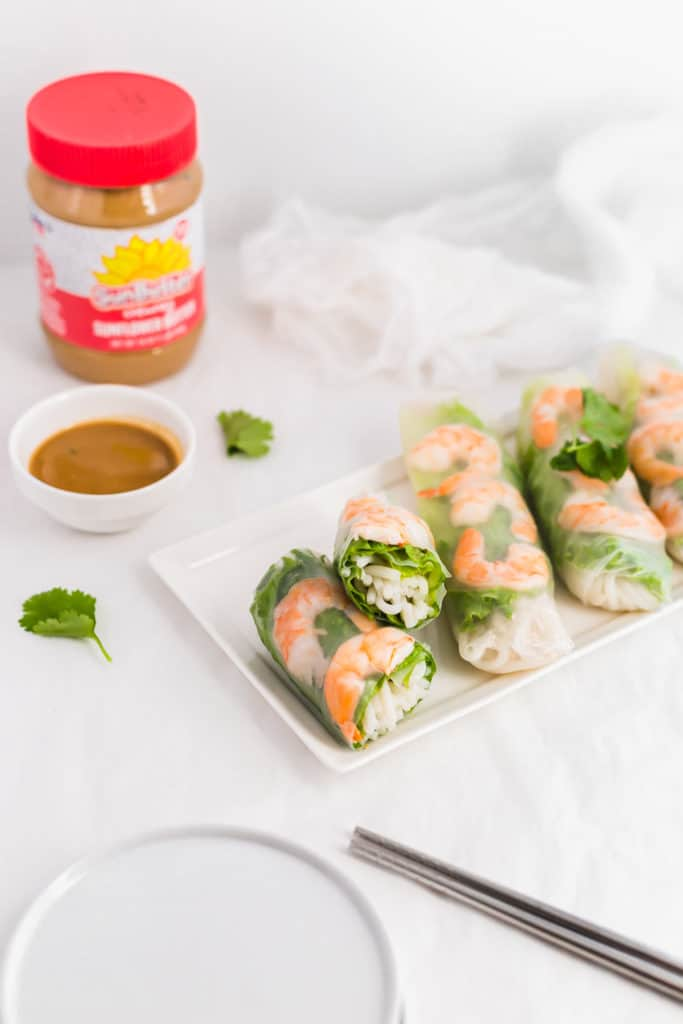 Vietnamese Salad Rolls on white rectangular plate with SunButter Dipping Sauce in small bowl, SunButter jar in background.