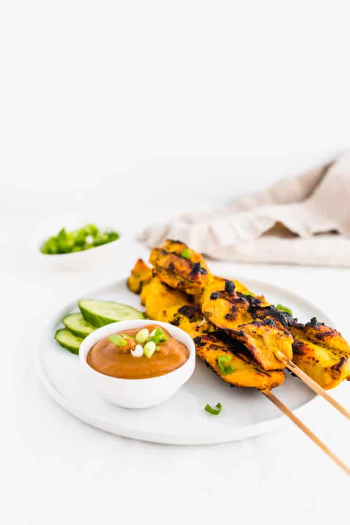 Skewers of chicken satay on white plate with SunButter sauce.