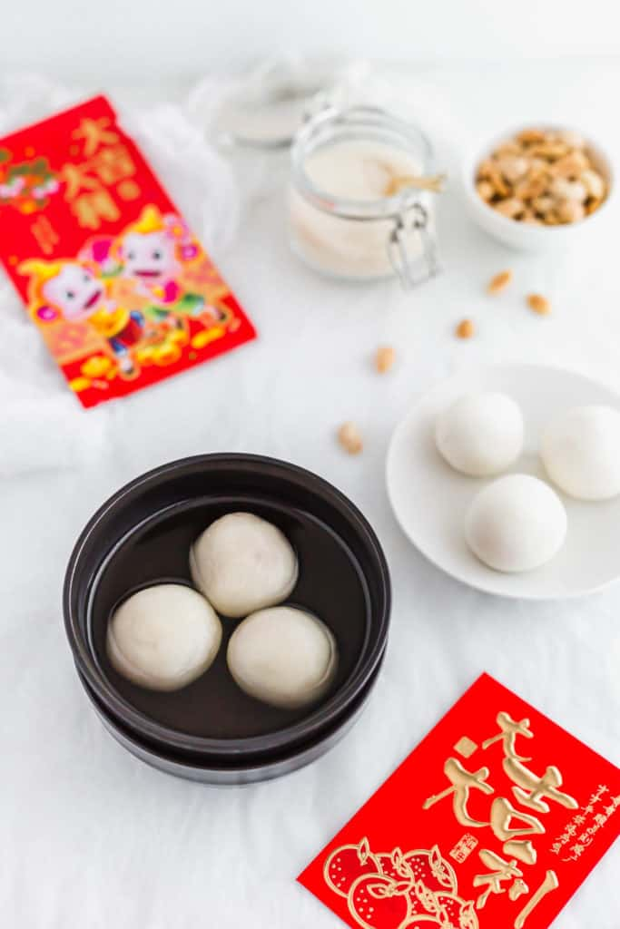 Cooked peanut tang yuan in soup in a black bowl, red envelopes, plate of uncooked tang yuan, peanuts on the side.