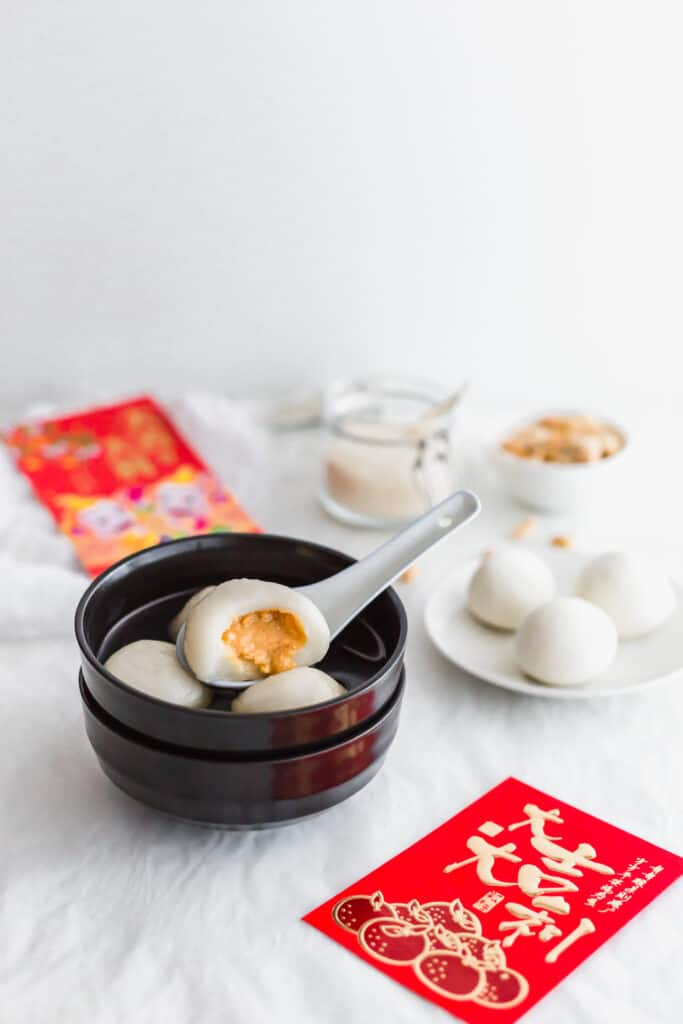 A bitten peanut tang yuan on a white spoon in a black bowl, red envelopes, plate of uncooked tang yuan, peanuts on the side.