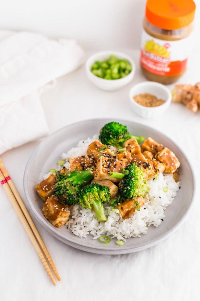 Asian Tofu Broccoli Stir Fry with SunButter Sauce on grey plate, chopsticks on side, SunButter jar in background.
