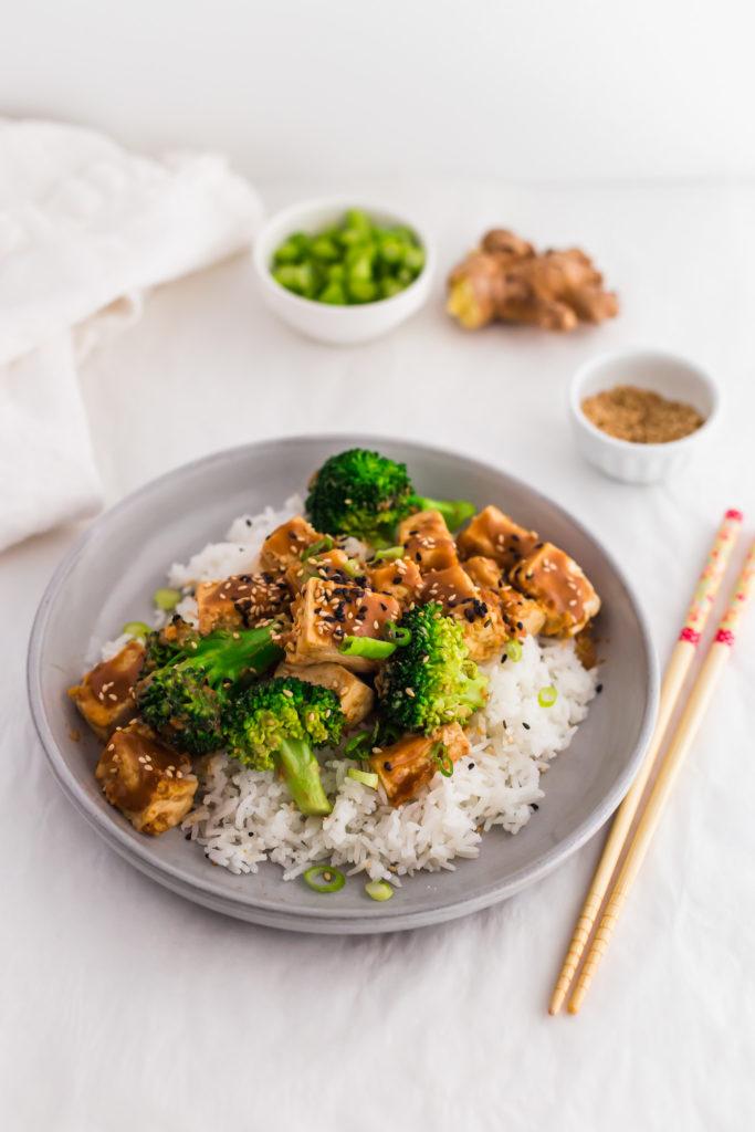 Asian Tofu Broccoli Stir Fry with SunButter Sauce on grey plate, chopsticks on side.