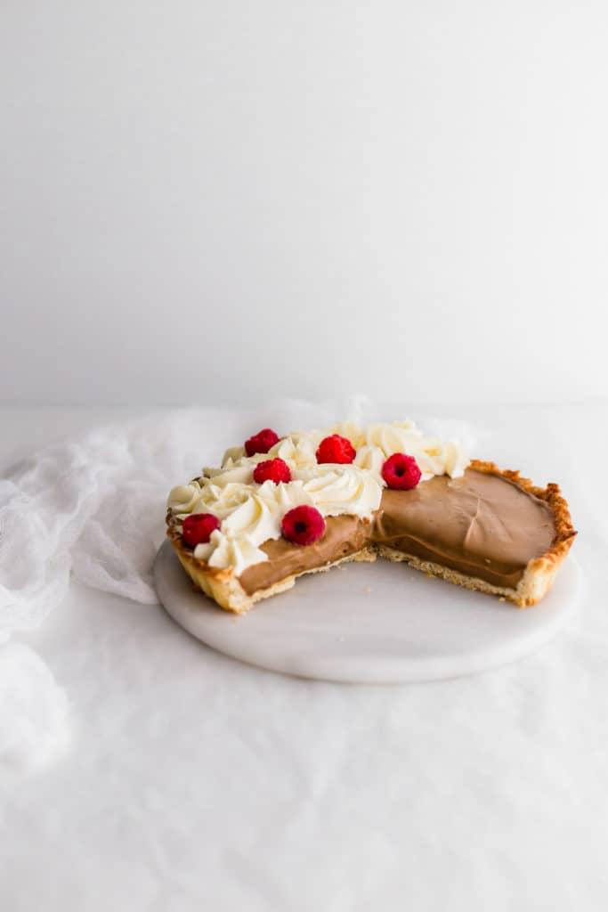 A cut open earl grey cream tart, on marble trivet.