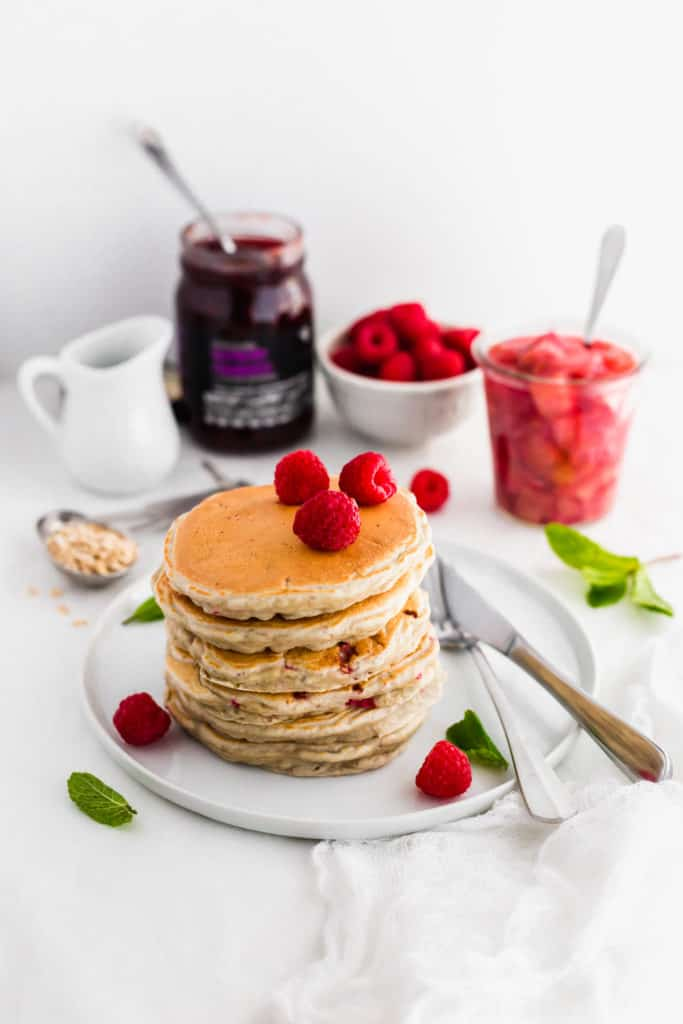 Stack of pancakes with raspberries on top on round white plate.