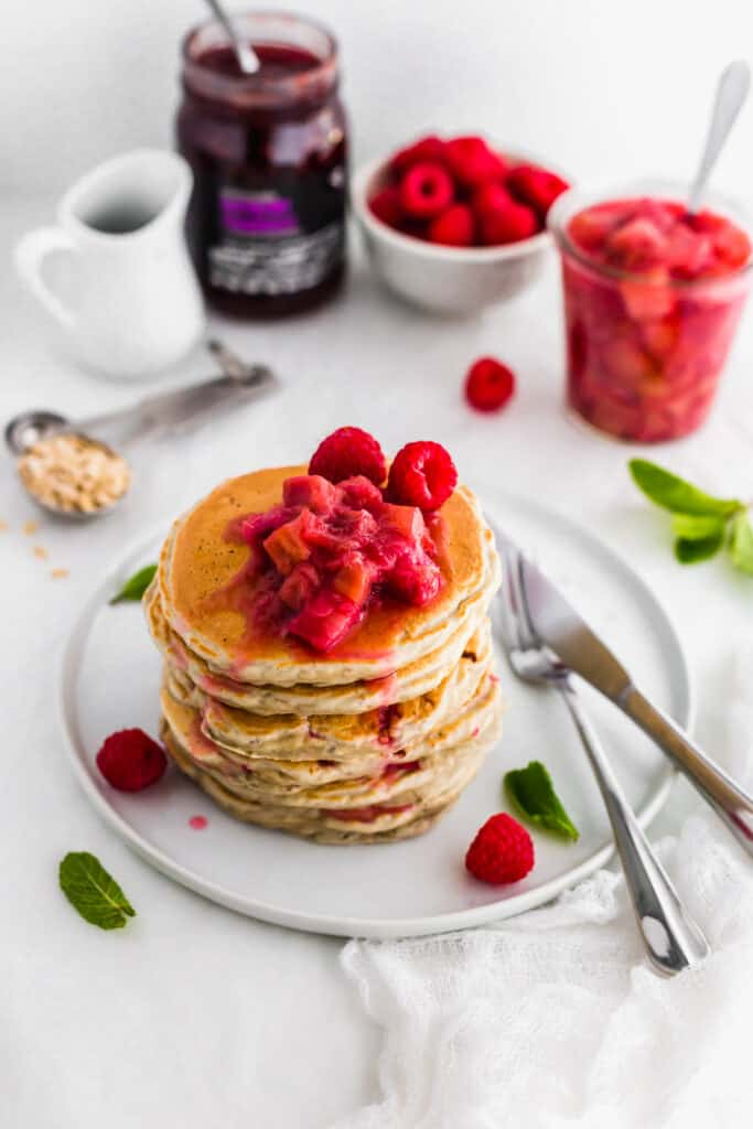 Stewed rhubarb on top of stack of pancakes on round plate with fork and knife.