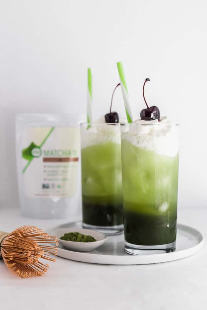 2 layered matcha cream soda in glass with cherry and green and white straws, tea packaging in background.