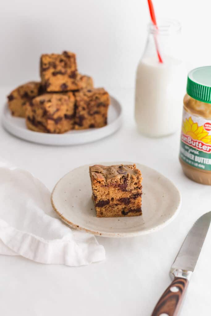 Cut SunButter chocolate cookie bar on small plate with knife, SunButter jar and milk with straw on the side.