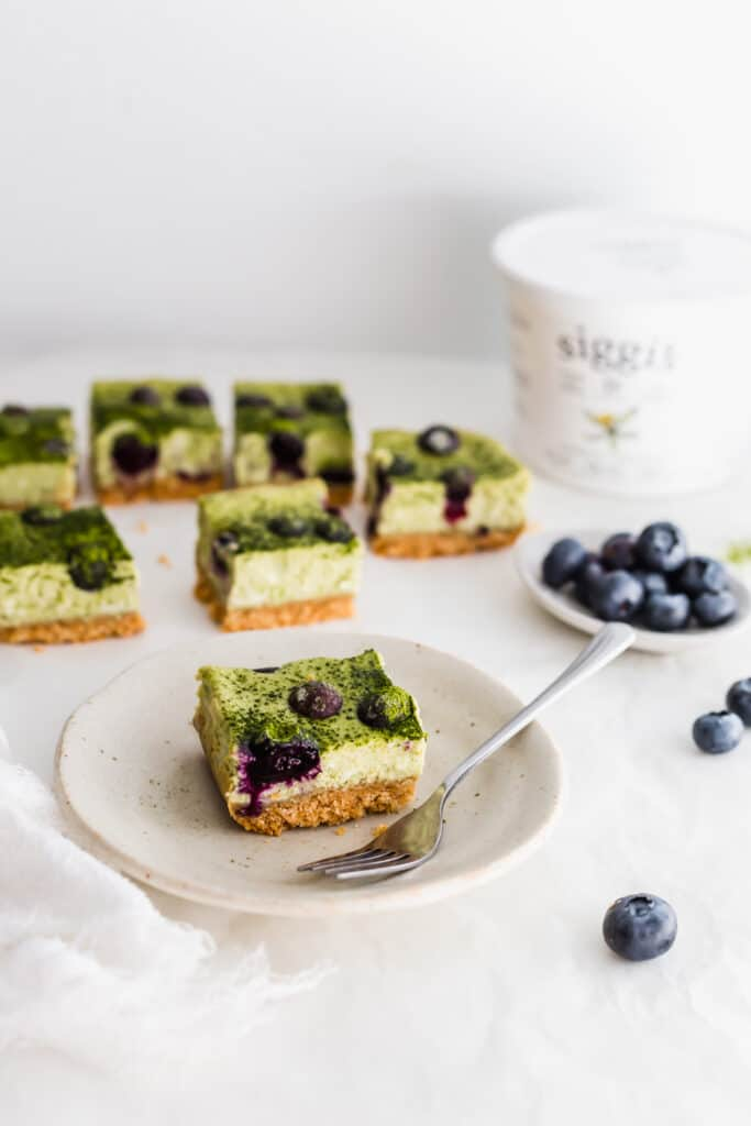 Matcha blueberry cheesecake bar on small plate with fork, blueberries on side, siggi's yogurt container in background.