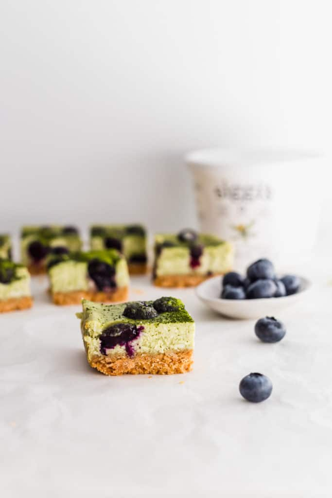 Matcha blueberry cheesecake bar with blueberries on side, siggi's yogurt container in background.