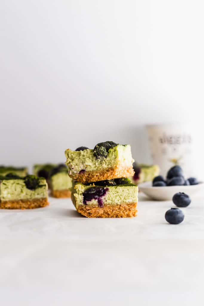 Stack of matcha blueberry cheesecake bars with blueberries on side, siggi's yogurt container in background.