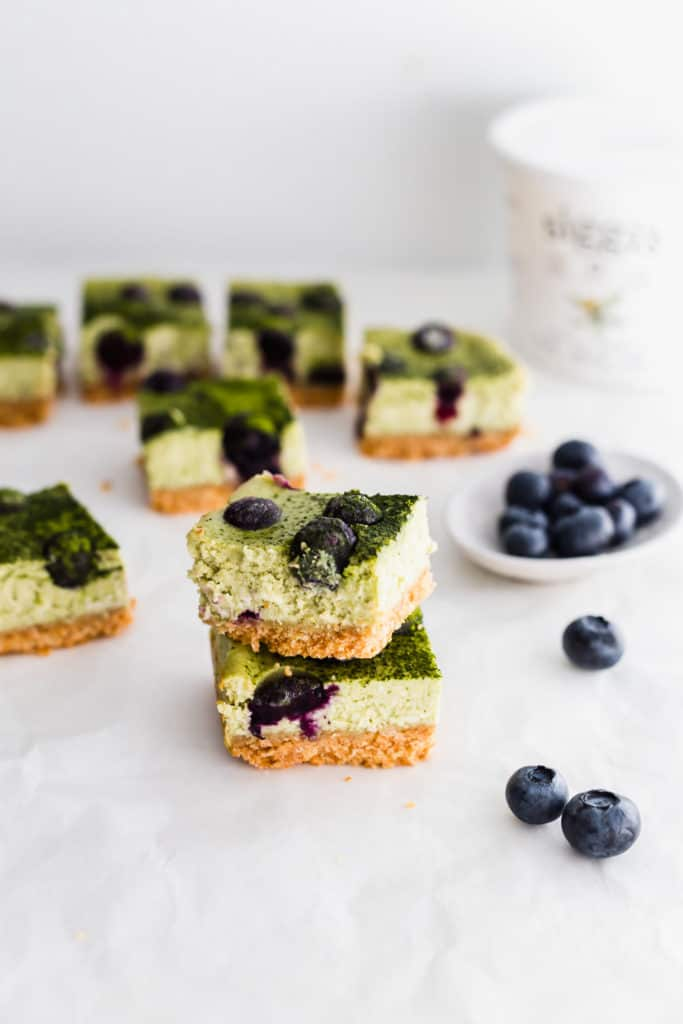 Stack of matcha blueberry cheesecake bars, with blueberries on side, siggi's yogurt container in background.