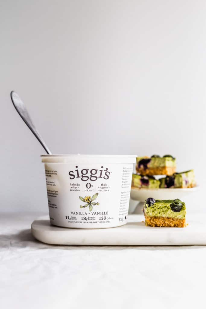 Container of siggi's yogurt with spoon on marble with matcha blueberry cheesecake bars on side.
