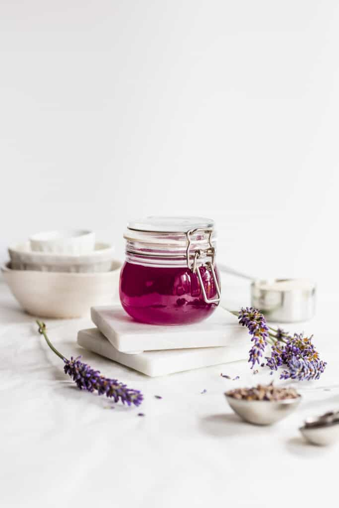 Jar of purple lavender syrup on marble coasters with sprigs of lavender flowers.
