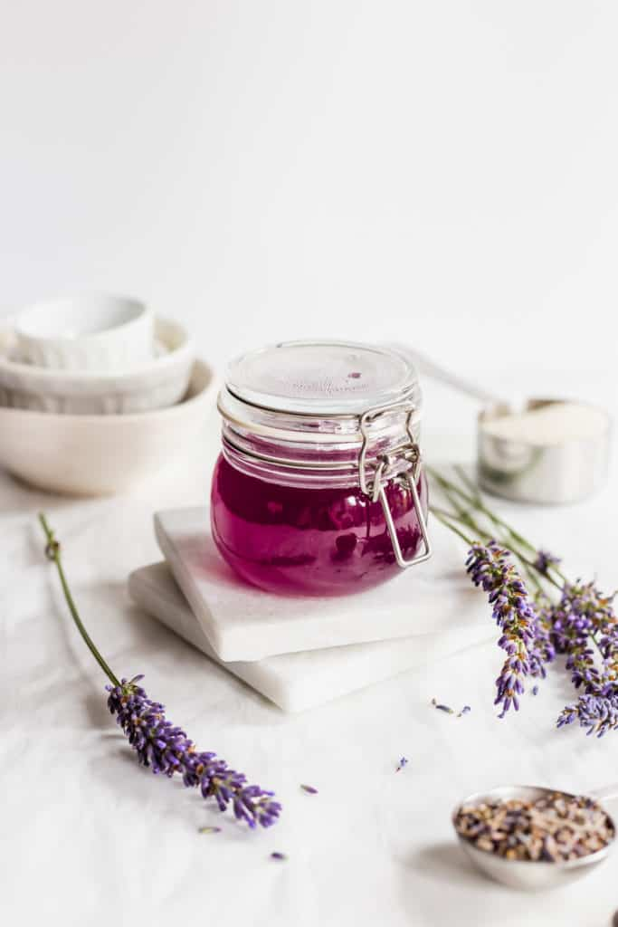 Purple lavender syrup in jar on marble coasters with sprigs of lavender.
