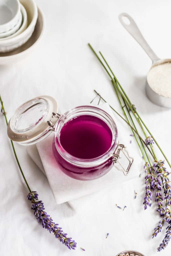 Open jar of purple lavender syrup on marble coasters with sprigs of lavender flowers, measuring cup filled with sugar on side.