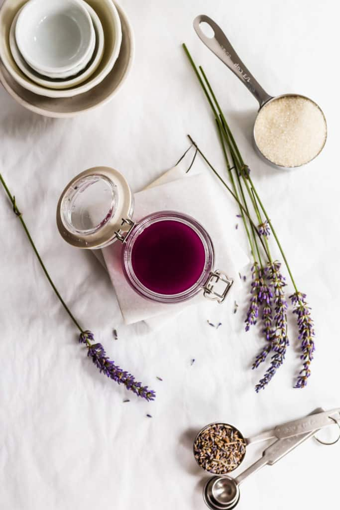 Open jar of purple lavender syrup on marble coasters with sprigs of lavender flowers, measuring cup filled with sugar on side, cup of sugar, measuring spoons on side.