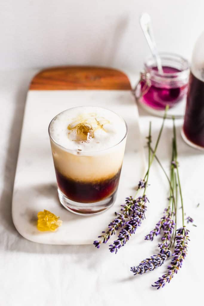 Glass of iced honeycomb lavender latte on marble with honeycomb and lavender flowers laying on the side.