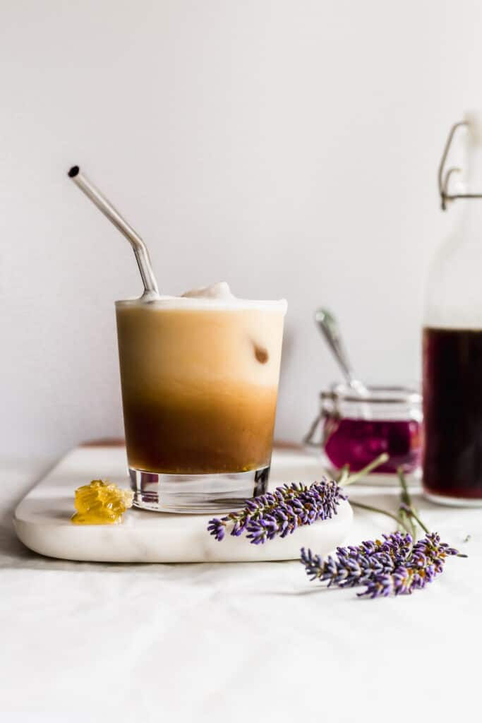 Glass of stirred iced honeycomb lavender coffee latte on marble with honeycomb and lavender flowers laying on the side, purple lavender syrup in background.