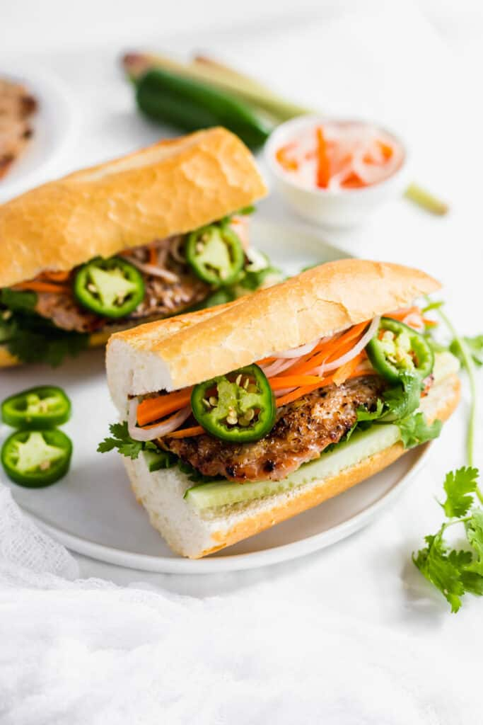 Close up of grilled lemongrass turkey banh mi sandwich on white plate with garnishes.