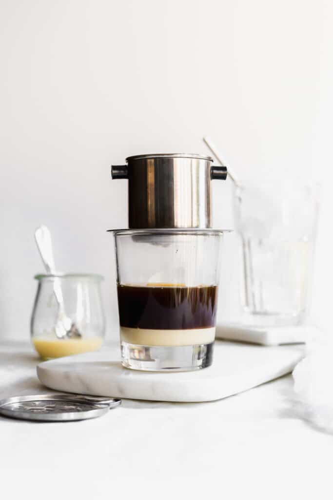 Layered coffee and condensed milk in glass with coffee phin on top, glass of ice behind, jar of condensed milk on side.