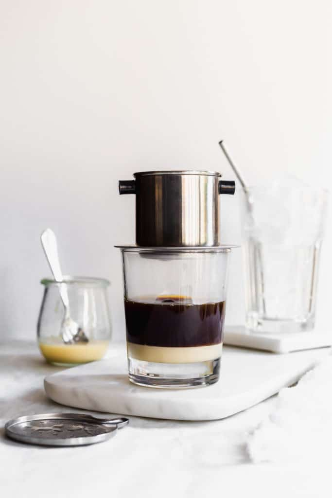 Layered coffee and condensed milk in glass with coffee phin on top, straw and glass of ice behind, jar of condensed milk on side.