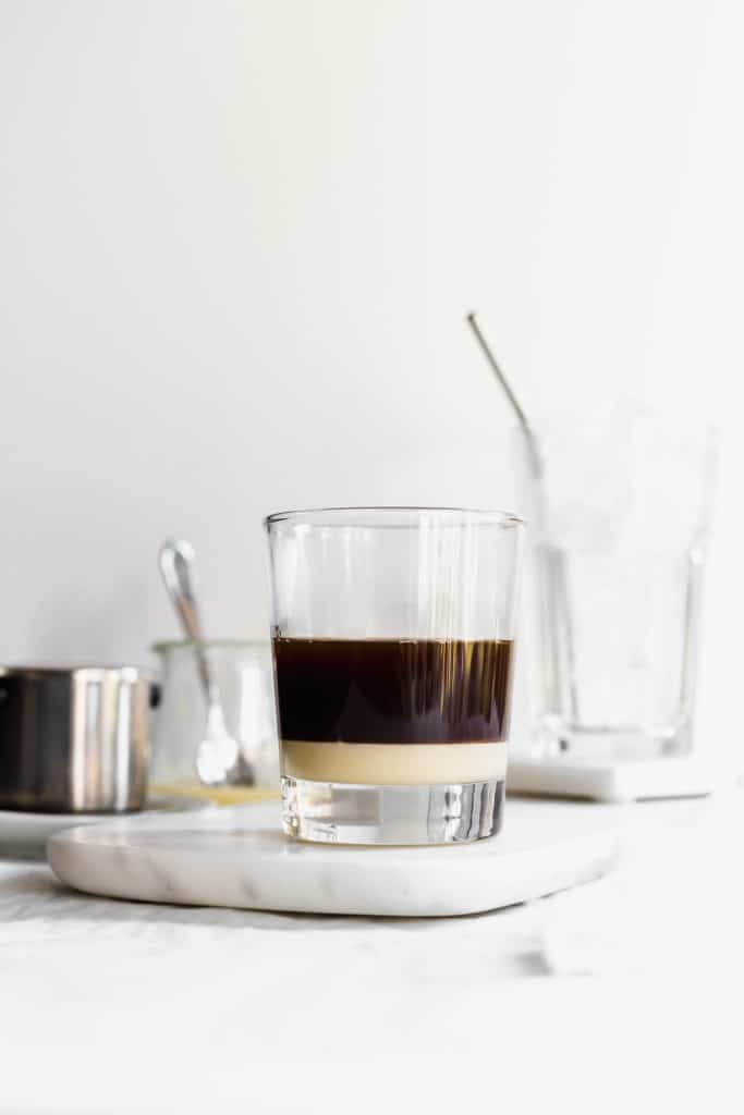 Layered coffee and condensed milk in glass on marble, glass of ice in background.