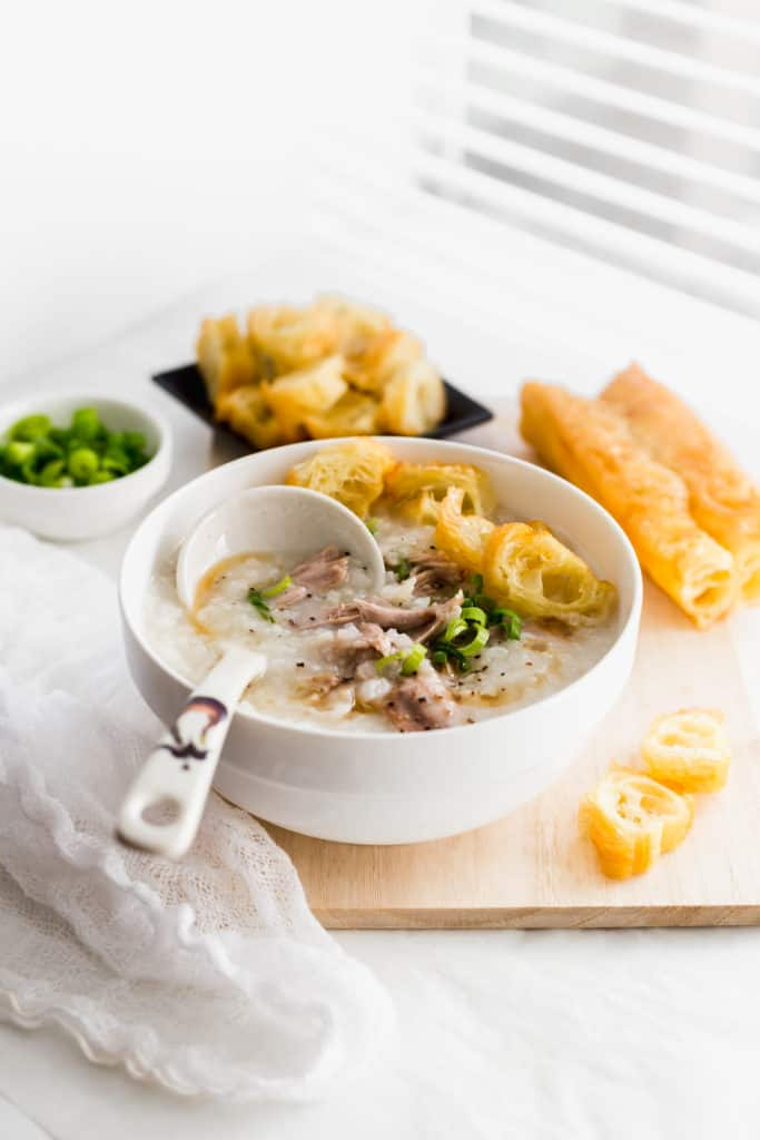 Rice congee with turkey and Chinese donut in white bowl with ladle on wooden board, donut in background.